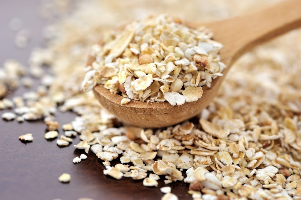 Oat flakes on a wooden spoon close-up